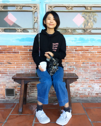 Photo of Ellen Chang sitting against a brick wall holding a Bolex and a mug of coffee.